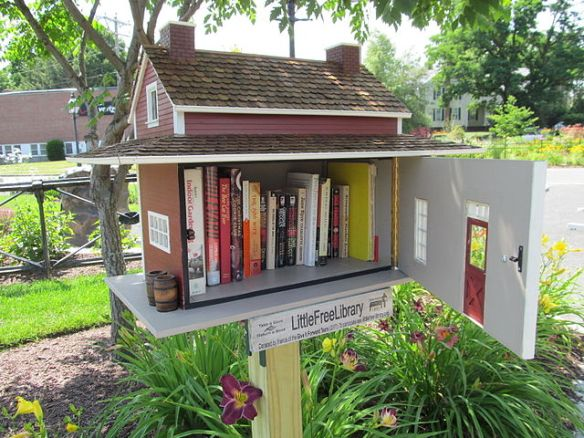A little free library, shaped like a miniature house filled with books, mounted on a post.